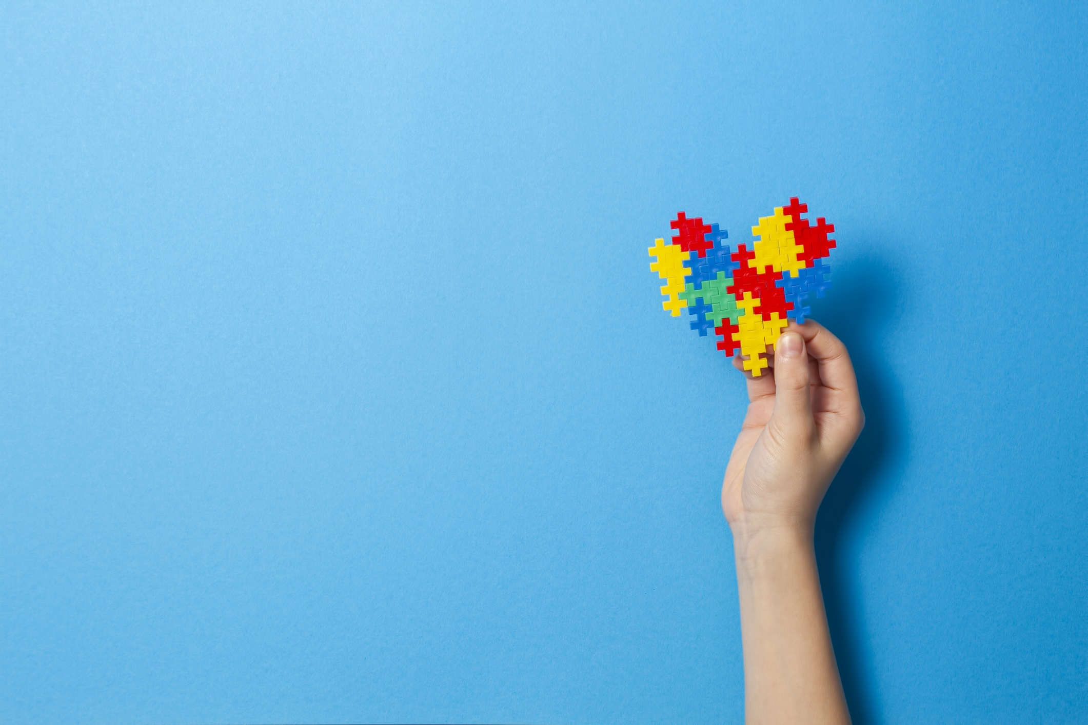 Kid hand holding multicolored heart on blue background. World autism awareness day concept