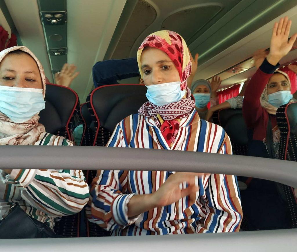 Temporeras despidiéndose de nosotras, esperando el embarque dentro de los autobuses en el Puerto de Huelva, el 18 de julio.