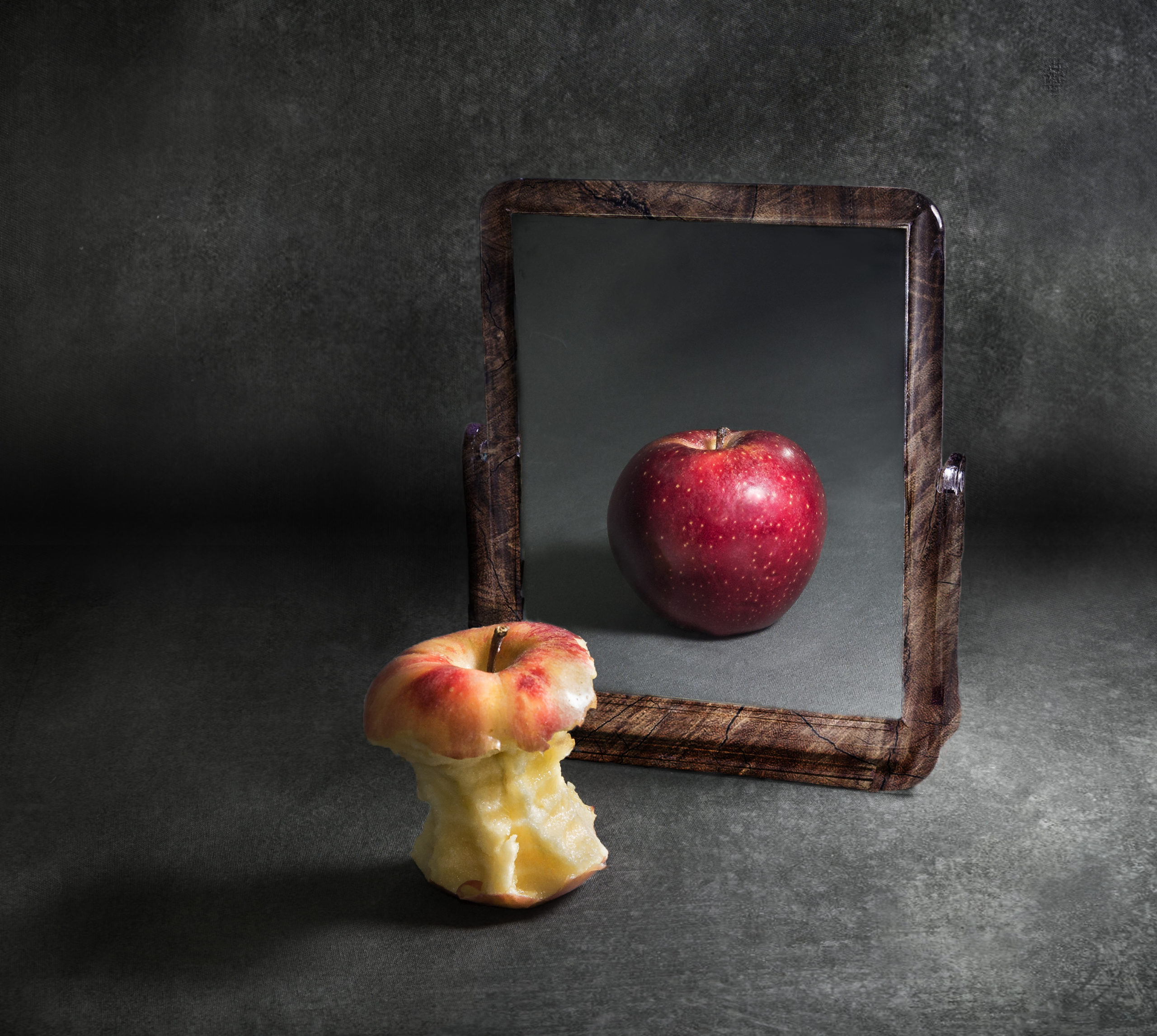 apple with anorexia looking at its reflection in a mirror With grey background