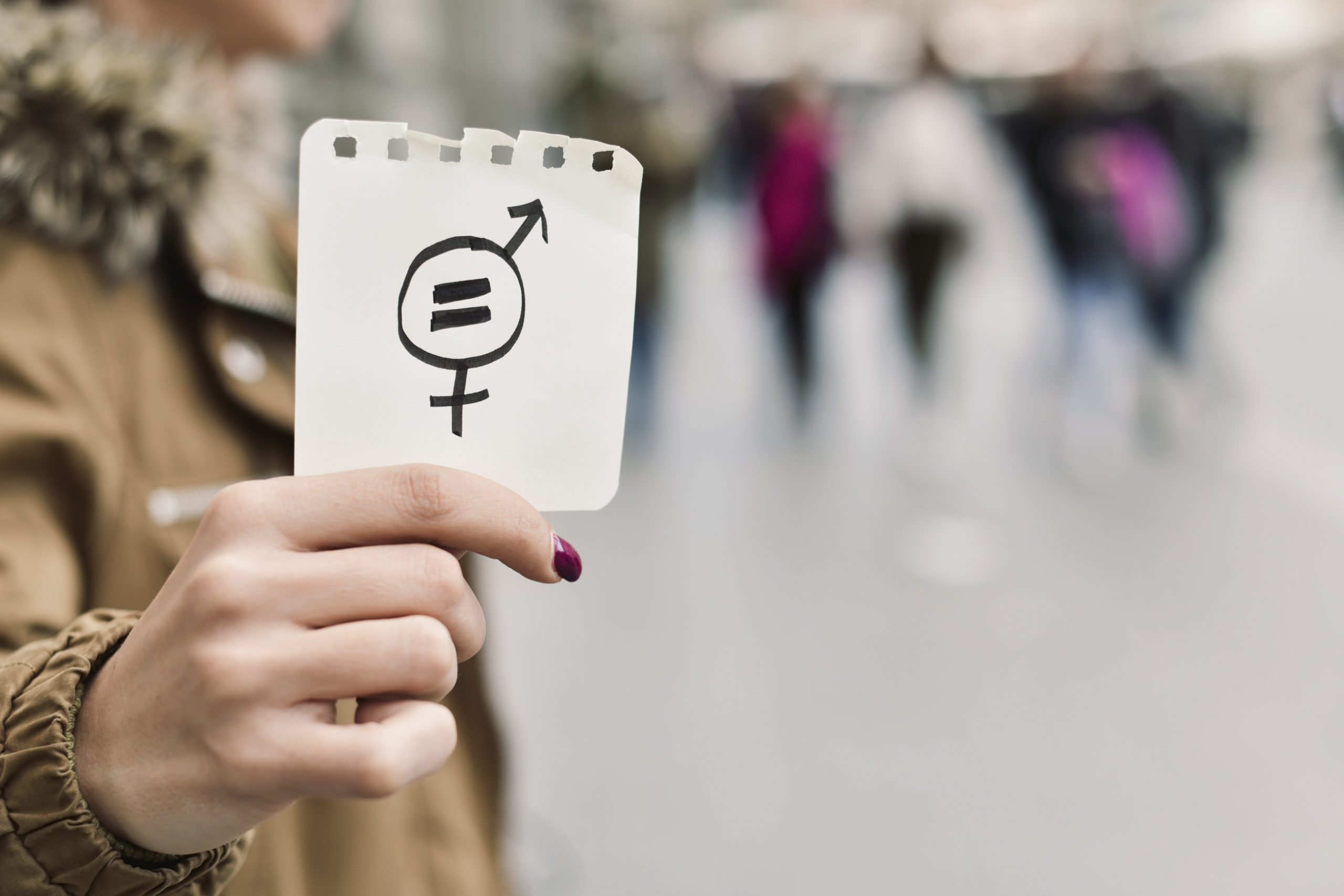 closeup of a young caucasian woman in the street showing a piece of paper with a symbol for gender equality drawn in it